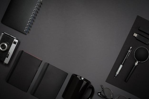 Natura morta, affari, forniture per ufficio o concetto educativo: immagine vista dall'alto di blocco note, telefono cellulare e tazza di caffè su sfondo nero, pronta per l'aggiunta o il mock up