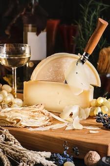 Still life di formaggio fresco pezzi di baguette uva e vino novello