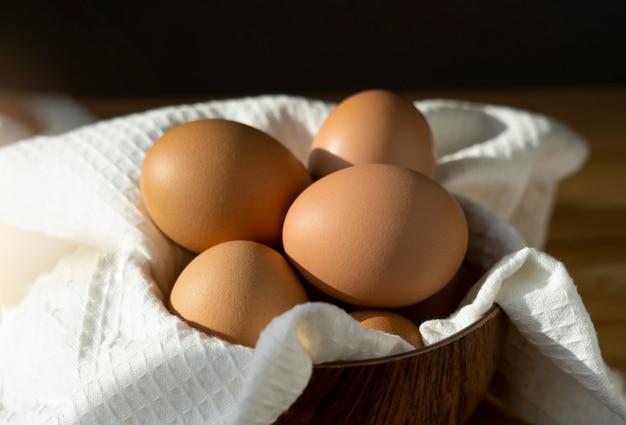 Natura morta delle uova di pollo in ciotola sulla tavola di legno nella cucina. gamma libera di uova, prodotti agricoli naturali. cibo sano durante
