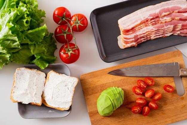 Composizione di natura morta composta da due panini, pomodori freschi, lattuga, avocado e vassoio con fette di pancetta sul tavolo della cucina