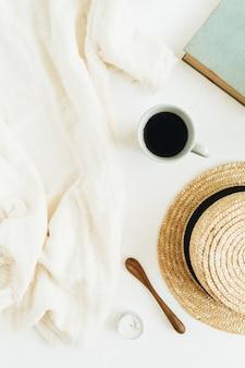 Composizione di natura morta con caffè, libro, cappello di paglia e coperta su superficie bianca