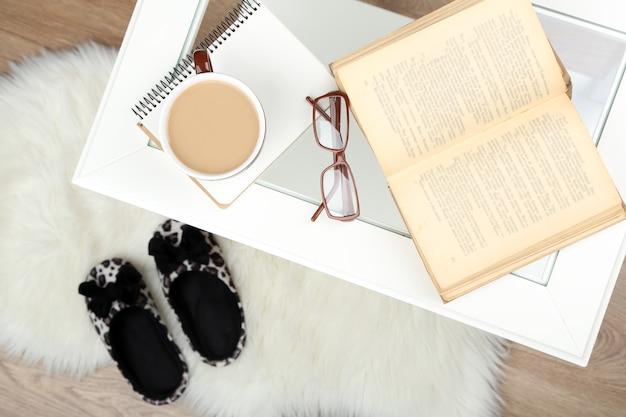 Dettagli di natura morta, tazza di caffè, libro e bicchieri sul tavolo, all'interno della casa