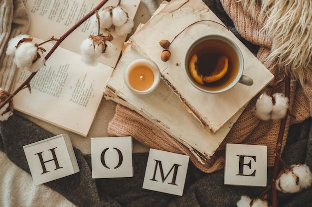 Dettagli di natura morta nell'interno della casa del soggiorno e la scritta home. libri e tazza di tè con cono e cotone. leggi, riposa. accogliente concetto autunnale o invernale, maglieria. accogliente concetto autunno inverno