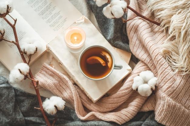 Dettagli di natura morta all'interno della casa del soggiorno. maglioni e tazza di tè con un cono, noci e decorazioni autunnali sui libri. leggi, riposa. accogliente autunno o inverno concetto.