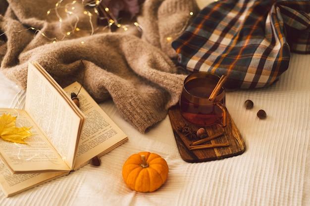 Dettagli di natura morta in maglioni interni domestici e tazza di tè con decorazioni autunnali e libri leggono resto