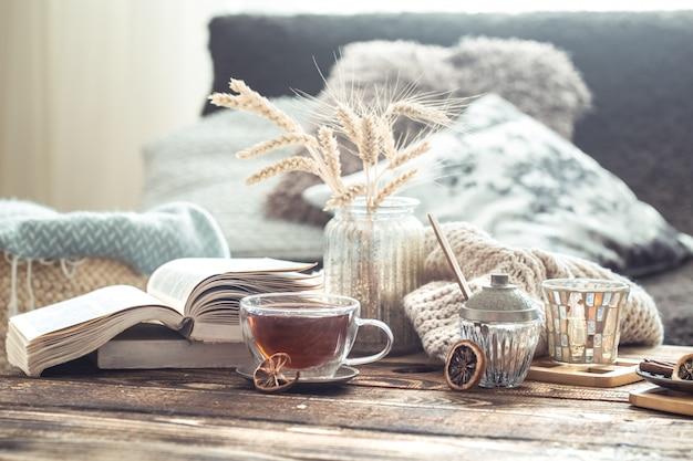 Dettagli di natura morta degli interni domestici su una tavola di legno con una tazza di tè