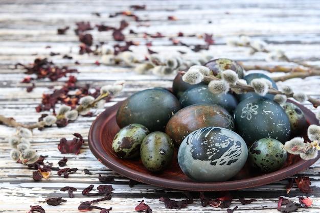 Natura morta di uova di pasqua su un piatto, dipinte con tè dai petali di una rosa sudanese o ibisco