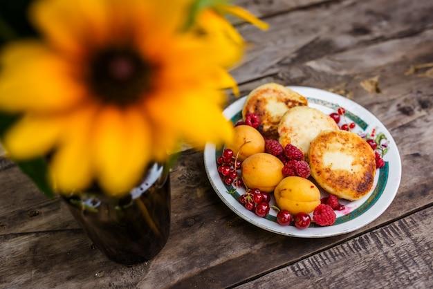 Natura morta di fiori e cottura con bacche su un tavolo di legno.
