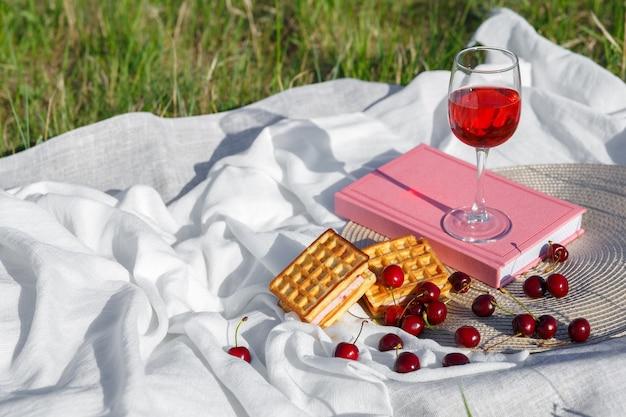 Still life e cibo foto cherry e waffle bacche giacciono su tovagliolo rotondo di vimini e tessuto wavecrumpled bicchiere di succo di ciliegia o vino