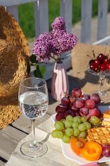 Foto di natura morta e cibo. picnic nella natura in una giornata di sole. piatto di frutta e cappello di paglia, un bicchiere di acqua limpida e un vaso con fiori lilla, stanno su un tessuto di tela su un vecchio pavimento di legno