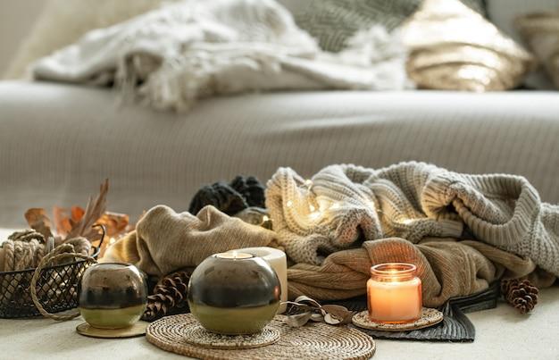 Natura morta di dettagli di decorazioni per la casa, candele, corde e vestiti caldi sullo sfondo.