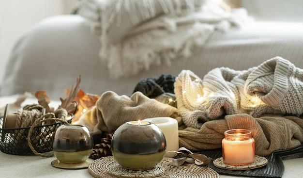 Natura morta di dettagli di decorazioni per la casa, candele, corde e vestiti caldi