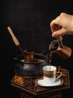 Natura morta di caffè orientale caldo sulla sabbia la mano femminile versa il caffè dal turco in una tazza