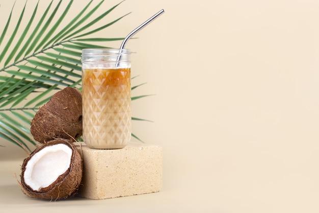 Natura morta americano ghiacciato con latte di cocco in un highball e un tubo di metallo su una pietra