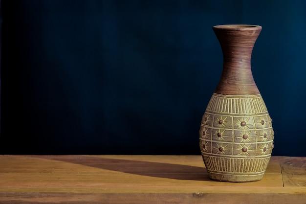 Vecchio barattolo dell'argilla di natura morta sulla tavola di legno.