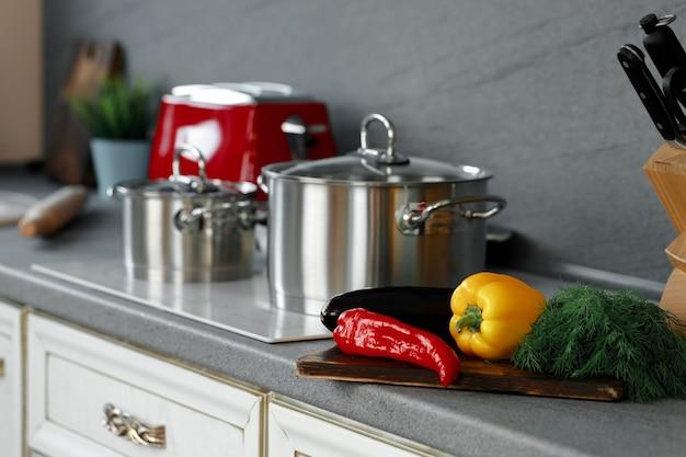 Foto still life di casseruole di metallo sul fornello a induzione in cucina