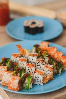 Piatti di natura morta con sushi giapponese rotoli su sfondo di cibo verticale tavolo in legno bianco per