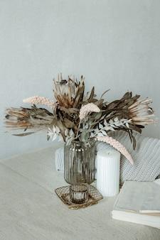 Natura morta in stile scandinavo con bouquet di fiori, elemento in maglia e dettagli decorativi.