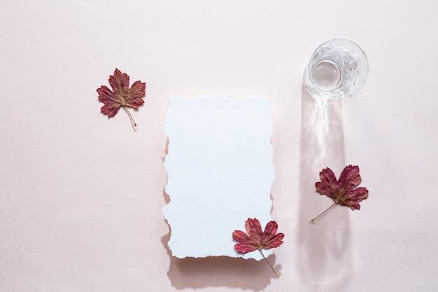 Scena di natura morta con un foglio di carta bianco e foglie colorate autunnali e un bicchiere d'acqua di cristallo