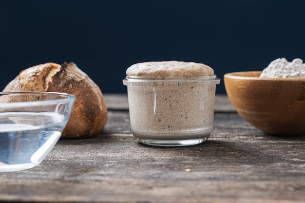 Natura morta con vasetto di lievito madre, tazza di acqua e farina e panino di pane fatto in casa