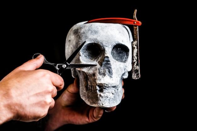 Cranio di natura morta con strumenti di rasatura. strumento del negozio di barbiere su sfondo nero