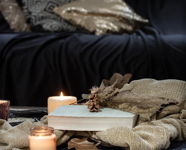 Natura morta sul tavolo con candele, libro maglione e foglie di autunno. accogliente soggiorno, arredamento d'interni per la casa.