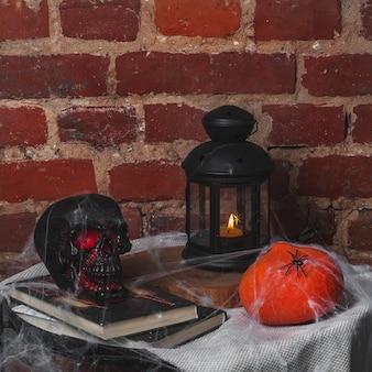 Natura morta sul tema della festa di halloween. un teschio, una zucca e dei libri sono distesi su un tavolo vicino al muro di mattoni. tutto è impigliato nelle ragnatele.