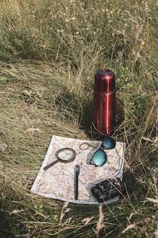 Natura morta di viaggiatore nell'erba con mappa e thermos