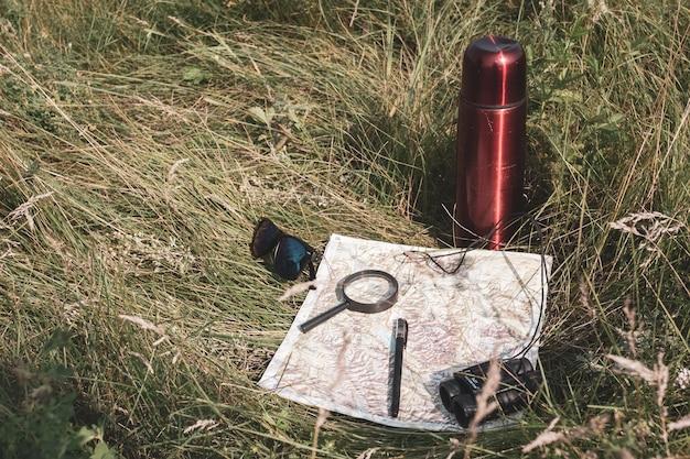 Natura morta di un viaggiatore con mappa e thermos