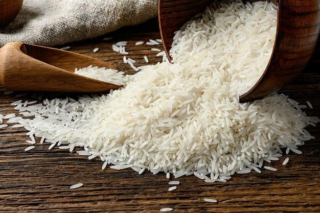Still-life di riso lungo crudo versato fuori dalla ciotola sul vecchio tavolo di legno.