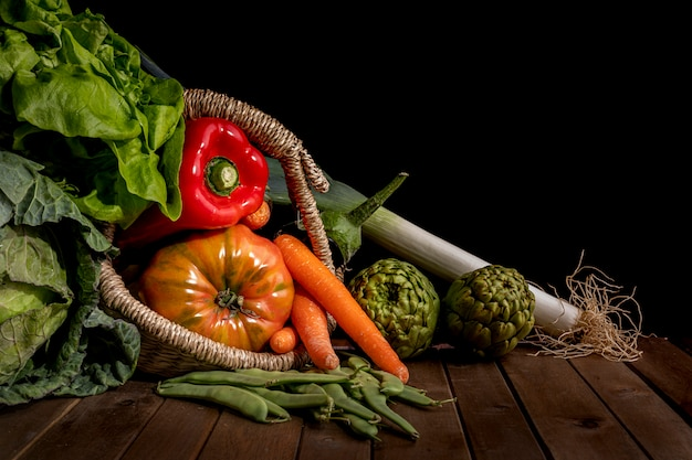 Natura morta delle verdure dal giardino sulla tavola di legno e sul fondo nero