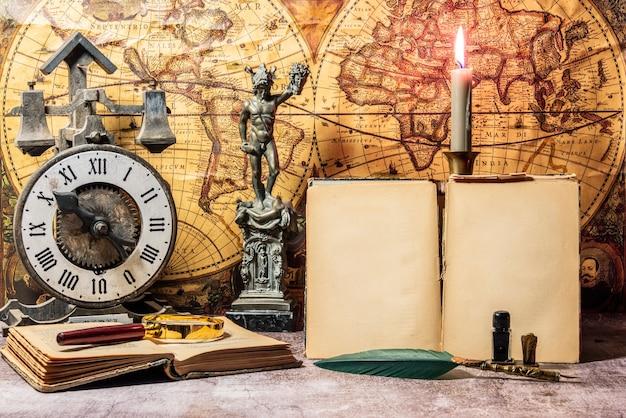 Still life wind-up clock e libri antichi su una mappa del mondo vintage