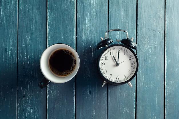 Natura morta con la sveglia e la tazza di caffè sulla tavola di legno