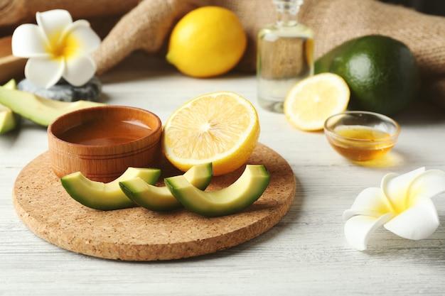 Natura morta con olio di avocado sul primo piano della tavola di legno