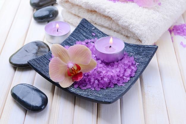 Natura morta con bellissimi fiori di orchidea in fiore, asciugamano e ciotola con sale marino, su fondo di legno di colore
