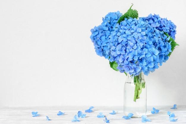 Natura morta con un bellissimo bouquet di fiori di ortensia blu con gocce d'acqua.