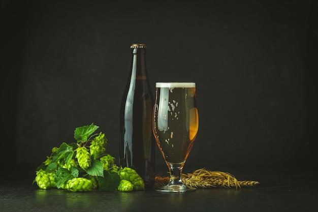 Natura morta con birra e pianta di luppolo in stile retrò. bicchiere di birra schiumosa fredda marrone bottiglia di birra e luppolo su uno sfondo scuro