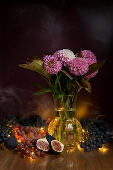 Natura morta con bouquet di fiori di dalie e uva e fichi. foto di alta qualità