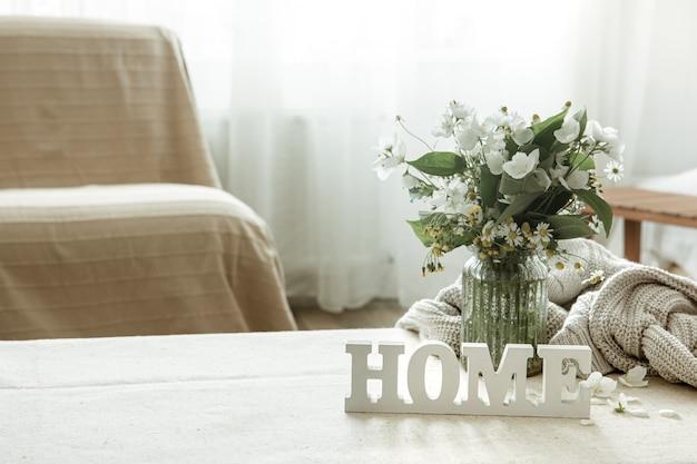 Natura morta con un mazzo di fiori, un libro e una casa di parole decorative in legno.