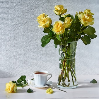 Natura morta con un mazzo di rose e una tazza di tè