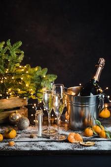 Natura morta con bottiglia di champagne in piedi in un secchio con ghiaccio due flute di champagne pieni luci a led ...