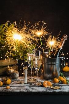 Natura morta con bottiglia di champagne in piedi in un secchio con ghiaccio due flauti di champagne pieni spumanti g...
