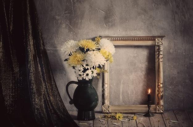 Natura morta con crisantemi e cornice in legno dorata su sfondo vecchio muro