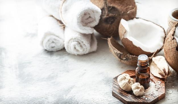 Natura morta con olio di cocco in una bottiglia e cocco fresco