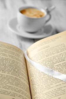 Natura morta con tazza di caffè e libro, primo piano