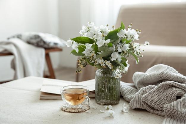 Natura morta con una tazza di tisana, un mazzo di fiori, un libro e un elemento a maglia su una superficie sfocata