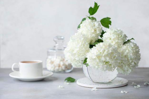 Natura morta con una tazza di tè o caffè, un barattolo di vetro di dolci e un mazzo di fiori bianchi in un vaso. concetto di mattina d'estate. immagine orizzontale. muro grigio chiaro