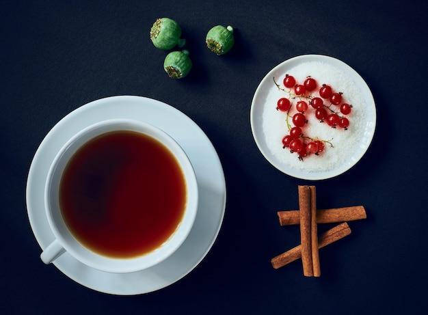 Natura morta con tazza di tè, ribes rosso, scatole di papaveri e bastoncini di cannella