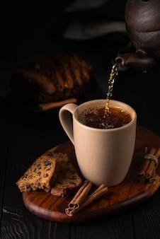 Natura morta con un cupcake e versando il tè in una tazza