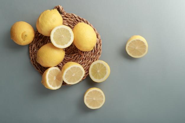 Natura morta con limoni interi e tagliati su uno sfondo liscio
